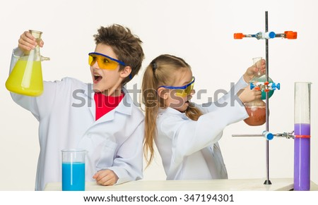 Two cute children at chemistry lesson making experiments on white background - stock photo