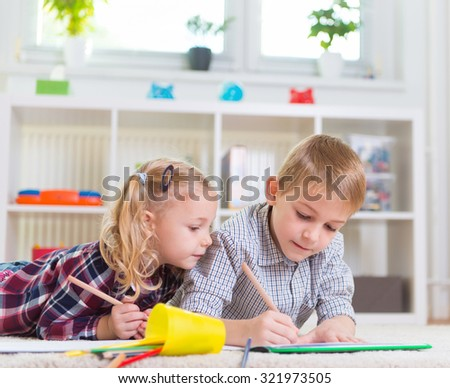 Two cute children draws on floor at home  - stock photo