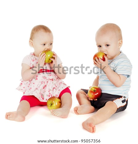 two cute children eating apples