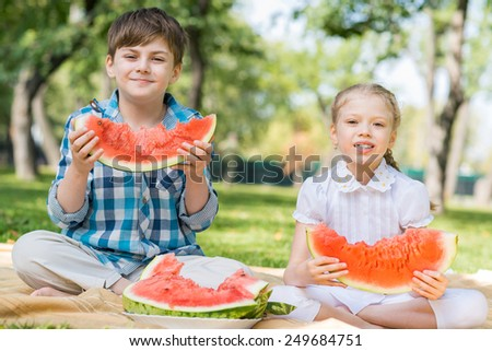 Two cute children in park eating juicy watermelon - stock photo