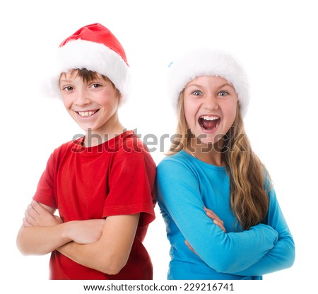 two cute children in santa hats are laughing, isolated over white