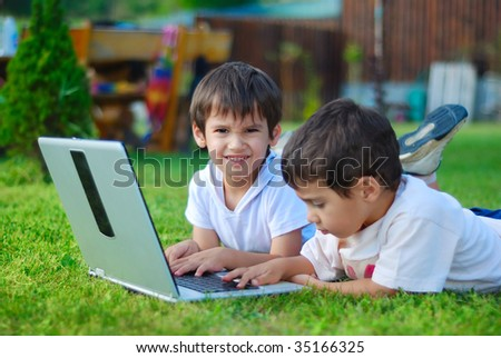 Two cute children laying in grass on laptop - stock photo