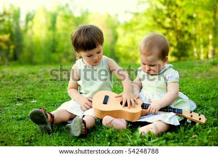 two cute children playing guitar together in the nature - stock photo