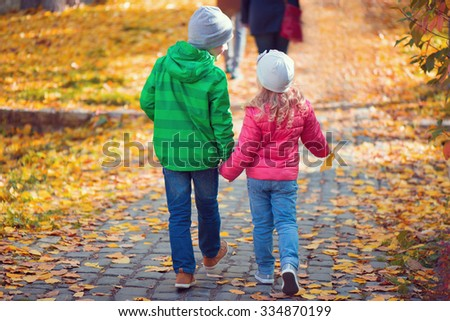 Two cute children walking in autumn town - stock photo