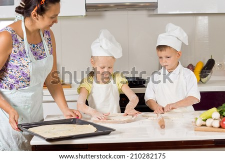 Two cute children wearing chef uniform while helping their mother to prepare the dough for baking a homemade pie, in the kitchen - stock photo