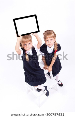 Two cute curious girl twins on white background sitting on a stool in smart dresses and holding in their hands the tablet. The picture with depth of field - stock photo