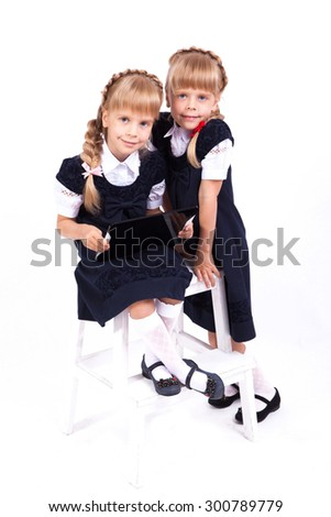 Two cute curious girl twins on white background sitting on a stool in smart dresses and holding in their hands the tablet. The picture with depth of field