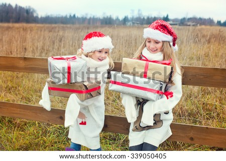 Two cute european sisters with gift boxes and Santa hats celebrate Christmas and New Year outside together happy - stock photo