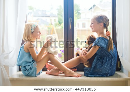 Two cute european toddler girls sitting near window at home playing teddy bears happy and funny. Colorful back yard at background - stock photo