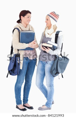 Two cute female students with books talking