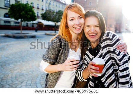 Two cute girlfriends stood in the empty cozy square European city. Girls are holding paper cups with coffee. Communication brings joy. In the background, beautiful architecture.