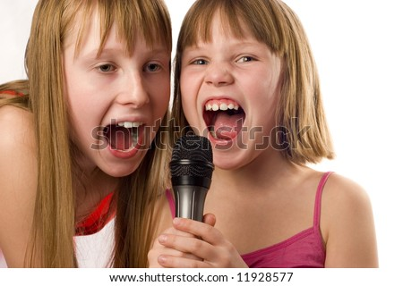 Two cute girls, 9 and 12 years age singing to microphone, isolated on white background - stock photo