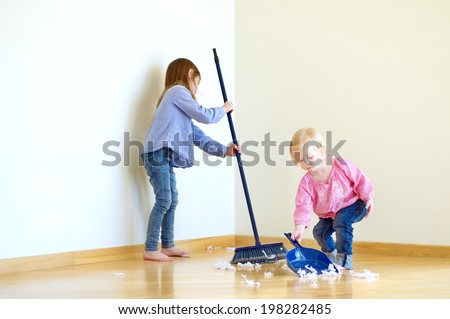 Two cute girls helping her mom to clean up - stock photo