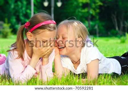 Two cute girls laughing on the green grass - stock photo