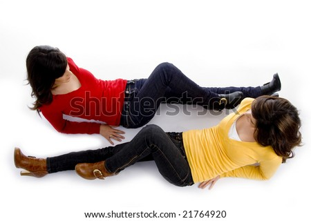 two cute girls lying opposite to each other on an isolated background - stock photo
