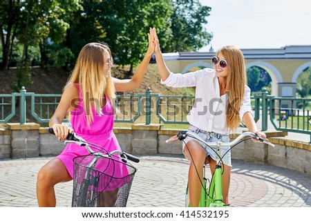 Two cute girls on bicycles in the summer give each other five
