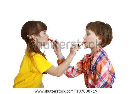 Two cute girls paint each other with lipstick isolated on white background. Makeup turns crooked and wrong