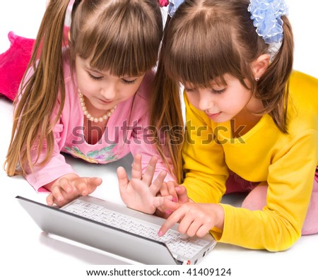 Two cute girls playing on laptop over white background - stock photo