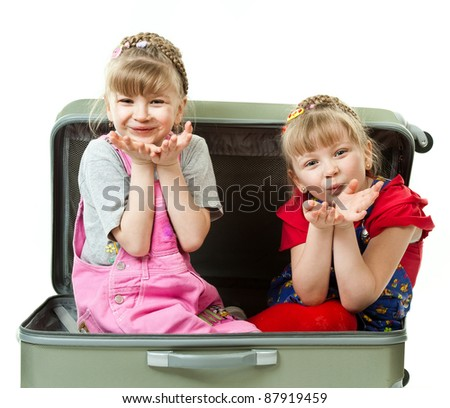 Two cute girls playing with a suircase isolated in white background - stock photo