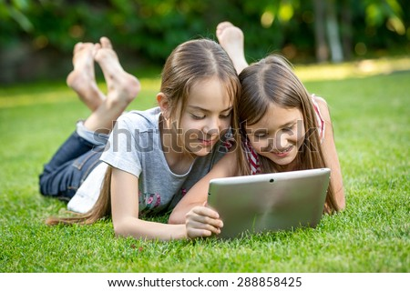 Two cute girls relaxing on grass at park and using digital tablet - stock photo