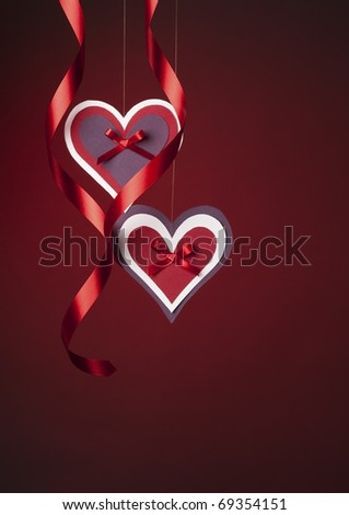 Two cute handmade paper hearts hanging from a string with ribbons on a red background.