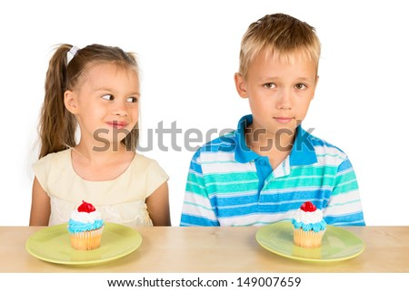 Two cute kids: a boy and a girl are sitting at the table with two delicious cupcakes in front of them, isolated - stock photo