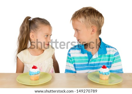 Two cute kids are looking at each other in a friendly way with two delicious cupcakes on a table in from of them, isolated - stock photo