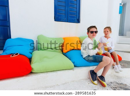 Two cute kids brother and sister drinking fresh smoothies on a colorful pillows at outdoor cafe on summer day - stock photo