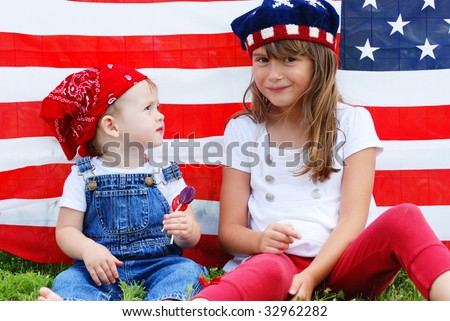 Two cute kids eating suckers next to an american flag - stock photo