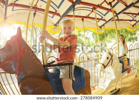 Two cute kids having fun while riding a carousel at an amusement park or carnival - stock photo
