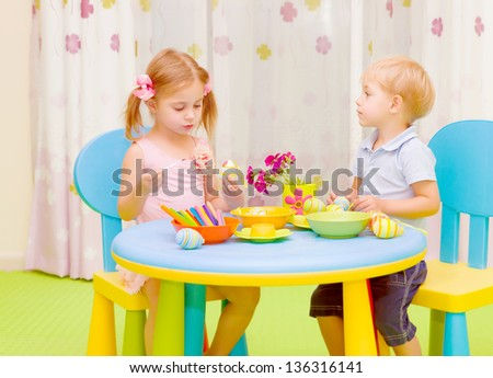 Two cute kids painted traditional Easter symbol, having fun at home, elementary school, art lesson concept