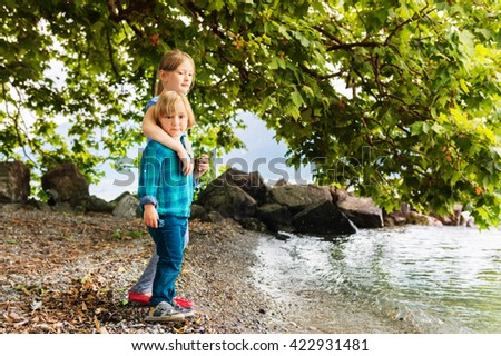Two cute kids playing outdoors by the lake, big sister hugging little brother - stock photo