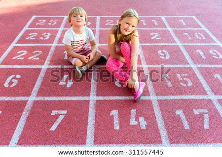 Two cute kids resting on school yard - stock photo