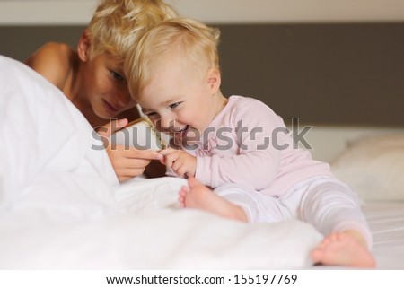 Two cute kids, teenager boy with little baby sister, are laying in parents bed playing electronic games on mobile smart phone - stock photo