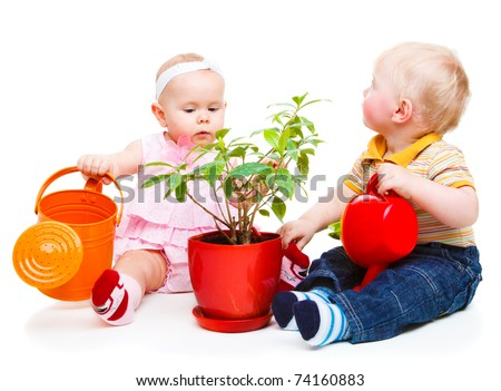 Two cute kids with watering pots beside a plant - stock photo