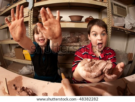 Two cute kids working with clay and playing around in a clay studio