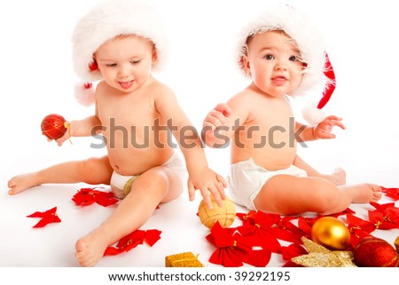 Two cute laughing babies in xmas hats - stock photo