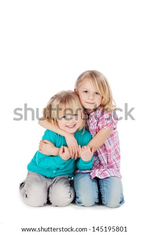 Two cute little blond sisters kneeling on the floor arm in arm cuddling each other in a loving embrace, on white - stock photo