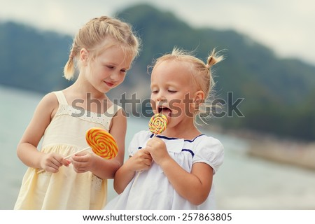 Two cute little blonde girls in white and yellow dresses eating bright orange Lollipops standing on the beach on a warm summer day. Holiday on a seashore concept. Funny kids. Sea. Ocean. - stock photo