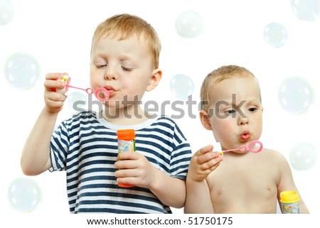 two cute little boys blowing bubbles on white background - stock photo