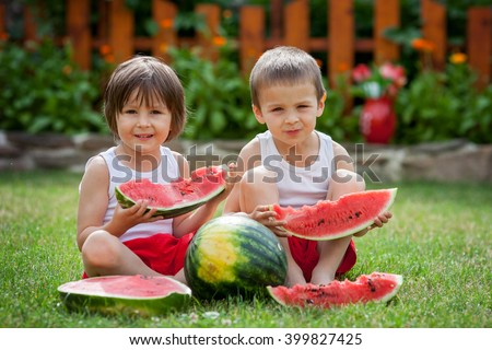 Two cute little boys, eating watermelon in the garden, summertime - stock photo