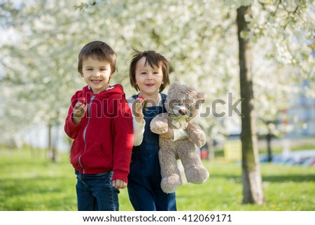 Two cute little children, boy brothers, eating strawberry in the park on a spring sunny afternoon, together with their big teddy bear - stock photo