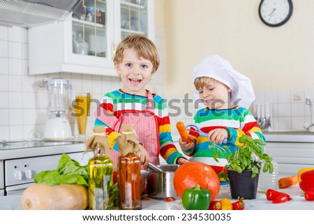 Two cute little children cooking italian soup and meal with fresh vegetables in home's white kitchen. Sibling boys in colorful shirts. - stock photo