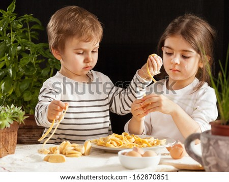 Two cute little children making dough for pasta. - stock photo