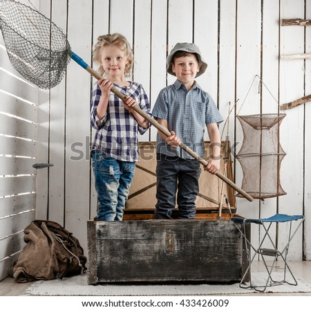 two cute little children standing in opened chest with net in hands - stock photo