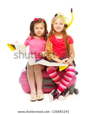 Two cute little exited girls sitting on suitcase with map preparing to travel wearing snorkel and mask, isolated on white
