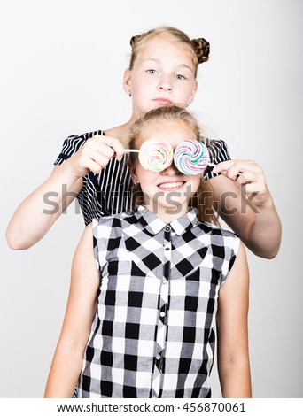 Two cute little girlfriend eating bright lollipops. Funny kids. Best friends pamper and posing - stock photo