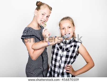 Two cute little girlfriend eating bright lollipops. Funny kids. Best friends pamper and posing
