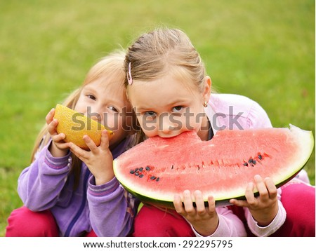two cute little girls eating watermelon  - stock photo