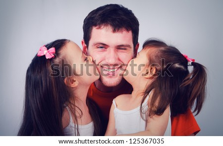 Two cute little girls kissing his happy dad - stock photo